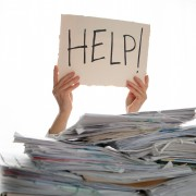 Person under a pile of papers with a hand holding a sign of help. Accounting.