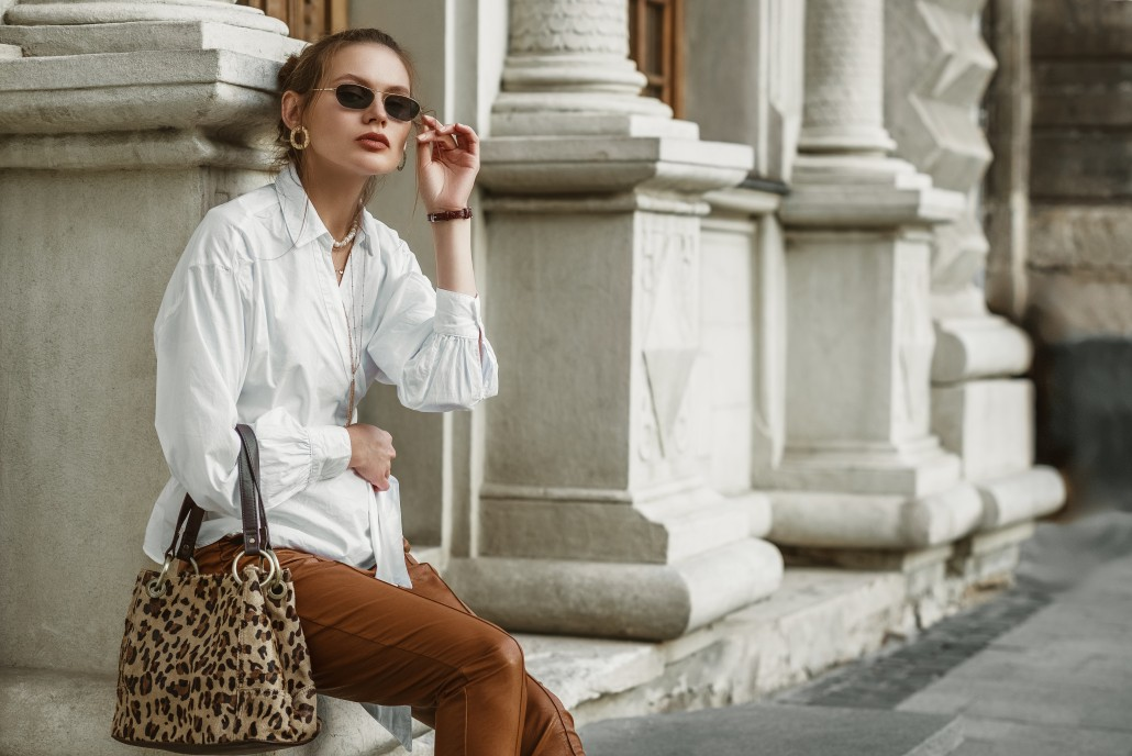 Outdoor autumn fashion portrait of elegant, luxury woman wearing sunglasses, trendy white shirt, leather trousers, holding animal, leopard print handbag, posing in street of European city. Copy space