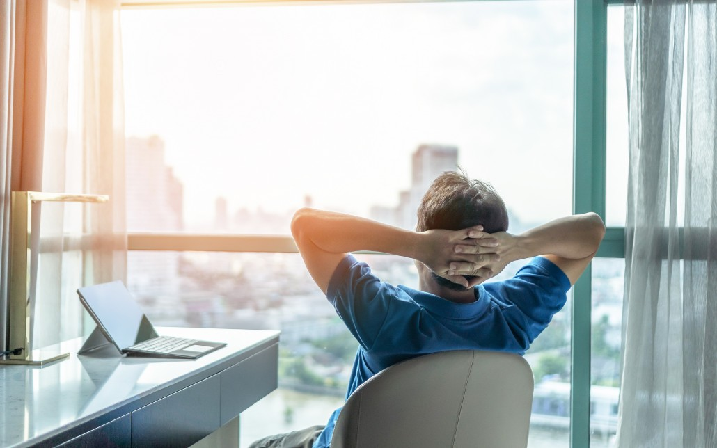 Life-work balance and city living lifestyle concept of business man relaxing, take it easy in office or hotel room resting with thoughtful mind thinking of life quality looking forward to cityscape