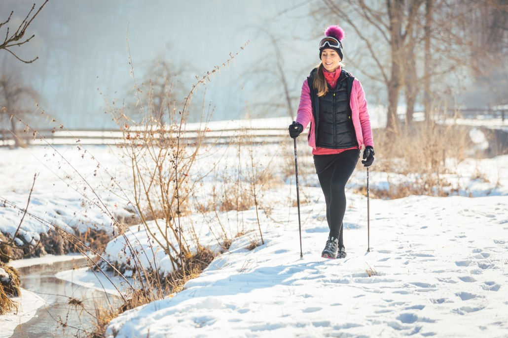 Fit woman Nordic walking in winter landscape