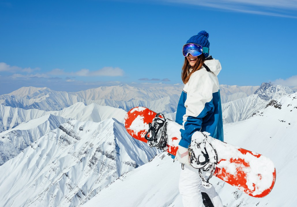 cheerful girl snowboarder on the background of peaks snowy mountains