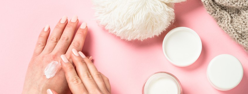 Woman using winter cream for hands.