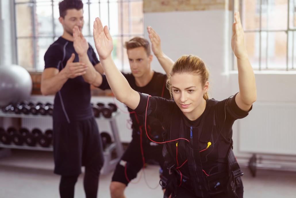 trainer und sportler beim ems-training im studio