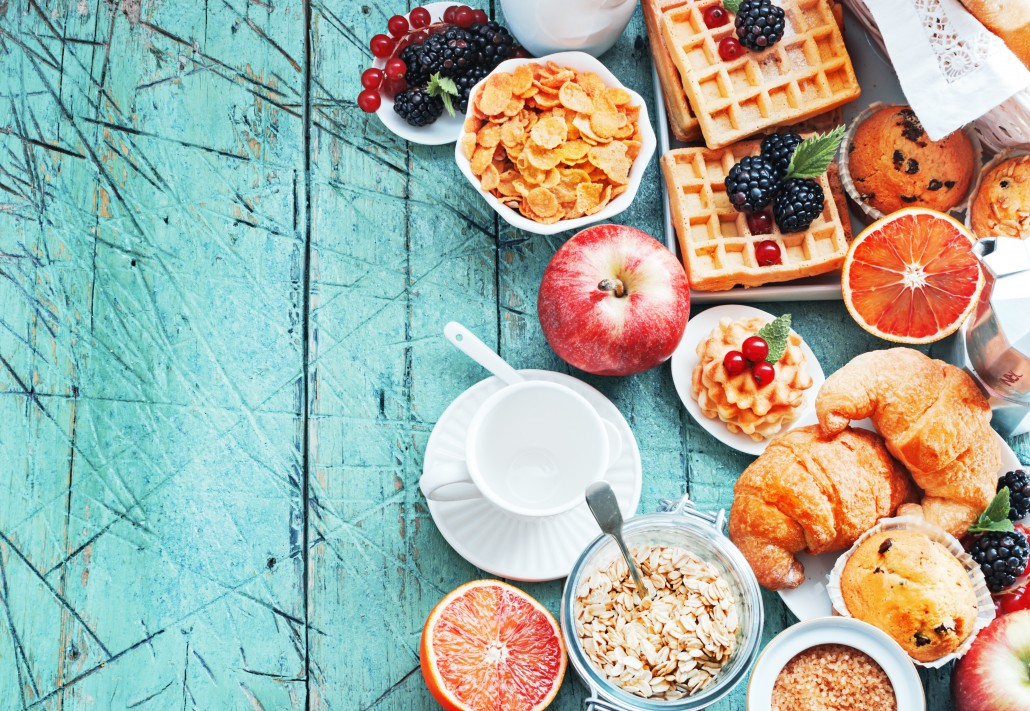 Healthy and colorful breakfast - cup of coffee with homemade granola, waffles, muffins,almond,hazelnuts,various fresh fruits, berries and milk on old wooden table.