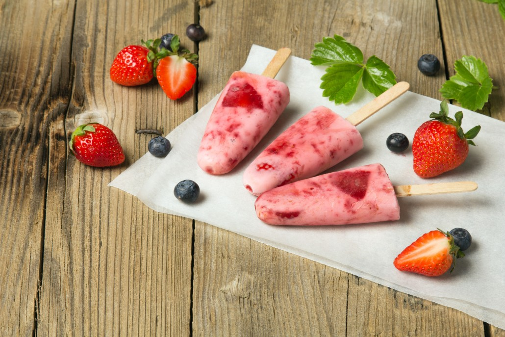 Fresh homemade strawberry ice cream on wooden background. Organic and vegan popsicles