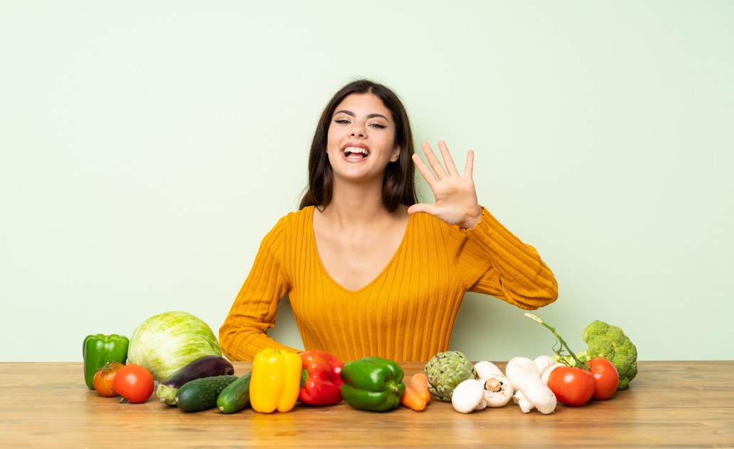 Teenager girl with many vegetables counting five with fingers