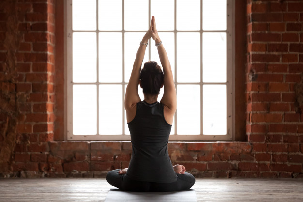 mujer-joven-haciendo-ejercicio-sukhasana-vista-trasera_1163-5085