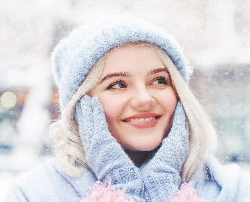 Close up outdoor portrait of young happy beautiful smiling girl touching her face. Model wearing winter hat and gloves