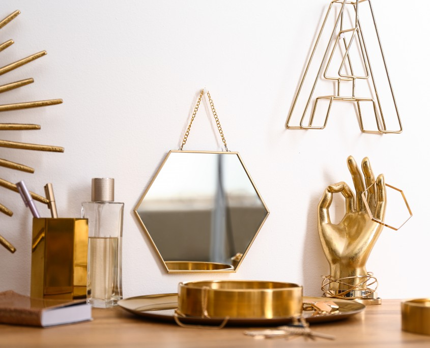 Composition with gold accessories on dressing table near white wall
