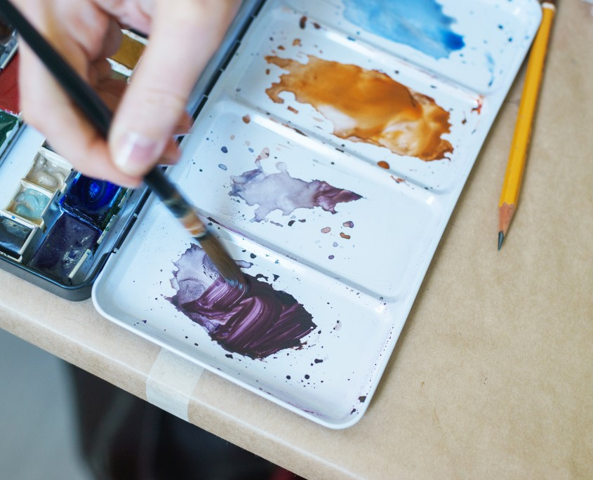 Artist paints with watercolor and kneads paints in a plastic palette.