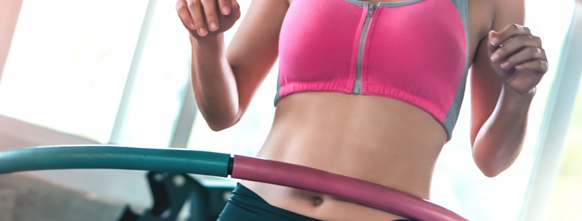 unrecognized Female in pink sportwear is working out with Hula hoop in fitness gym for healthy lifestyle concept