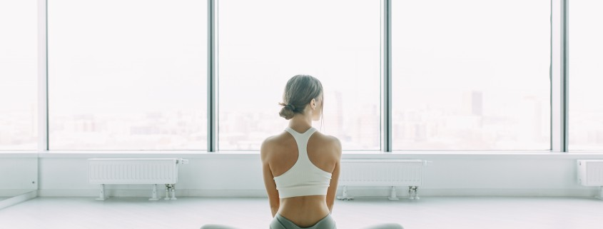 Relaxed posture during meditation. The girl is sitting on the Mat, relax. Exercises for self-control in yoga. White Windows with a panorama of the city.