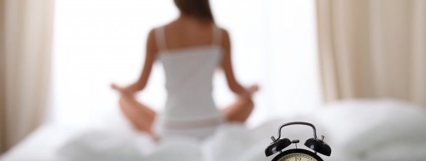 Alarm clock standing on bedside table has already rung early morning to wake up. Woman do yoga in bed in background. Early awakening, healthy lifestyle contemplation concept.