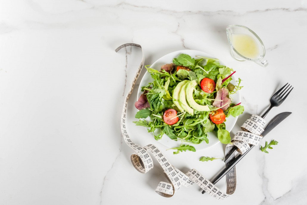 Healthy balanced diet concept, weight loss, calorie counting. Plate with green salad leaves, tomatoes, avocado with yogurt dressing, white table, with fork, knife, measuring tape, top view copy space