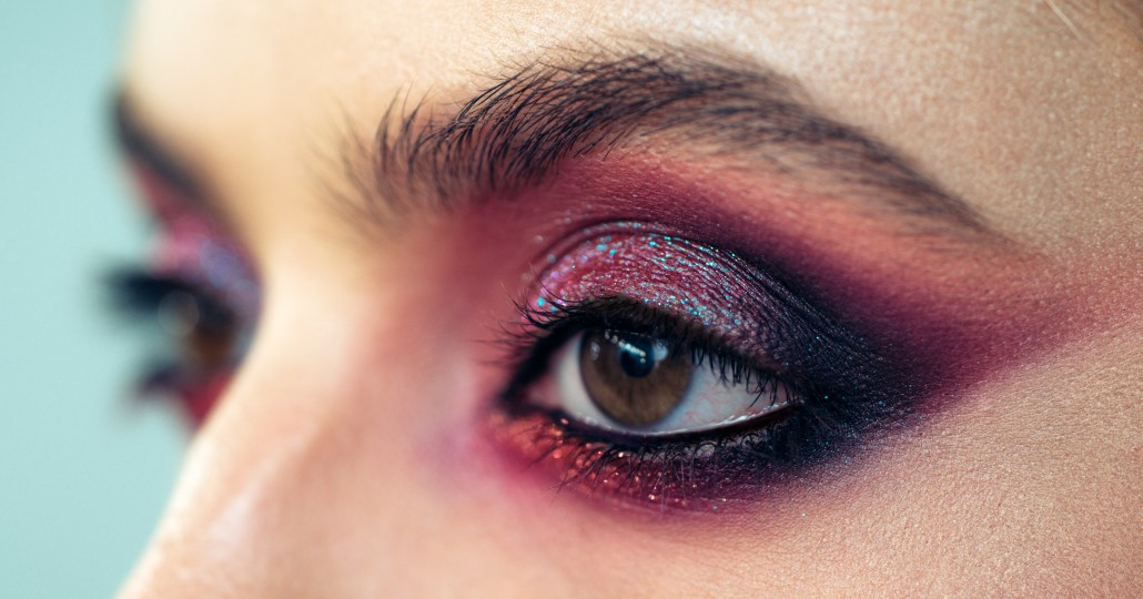 Professional smokey eyes make up at beautiful girl for special occasion. Shiny glitter pigments in eyes make up. Luxury eye makeup concept. Purple smokey eyes makeup close up photo.