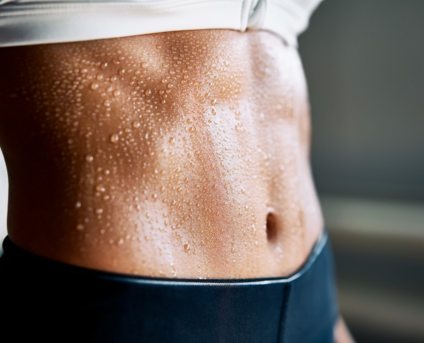 Close up of fit woman torso with sweat on skin after workout