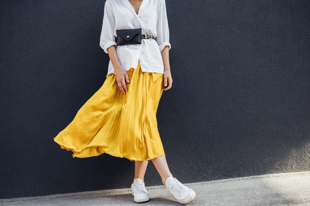 Horizontal cropped body image of beautiful slim woman in beautiful yellow skirt. Caucasian female fashion model standing over gray wall background outdoor with copy space.