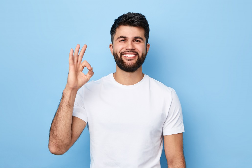 positive bearded man in white T-shirt showing ok sign