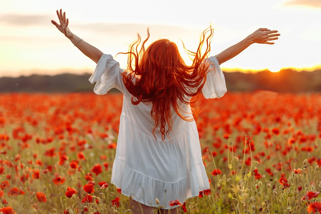 Happy redhead smiling woman in white dress on field of poppies at summer sunset