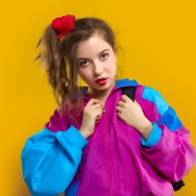 Fashion DJ girl in colorful trendy jacket from 90s. Teenager Girl shows strong face at the disco party of 80s vibes. Fashionable young model on yellow color background.