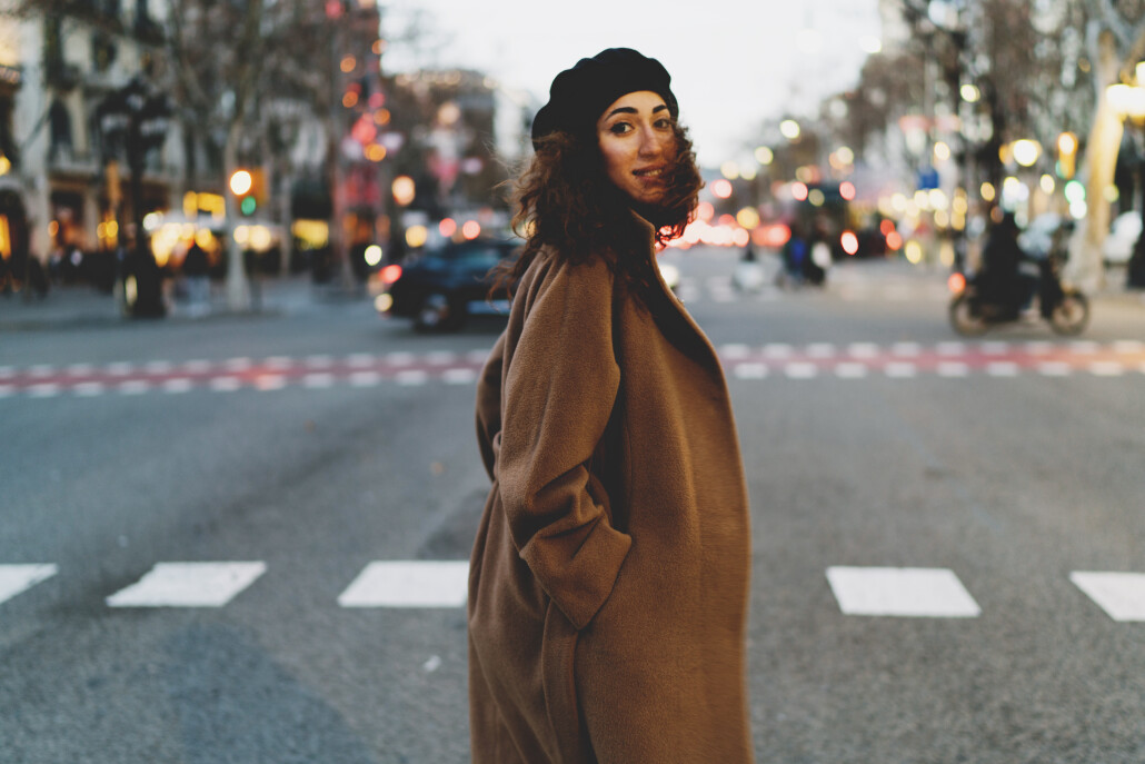 Elegant business woman with curly hair enjoying walking the city after hard working day. Student girl in a trendy clothes crossing the road. Hipster girl wearing oversized coat looking at the camera.