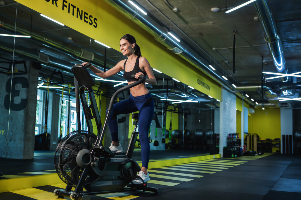 Smiling lady is exercising on machine in fitness studio