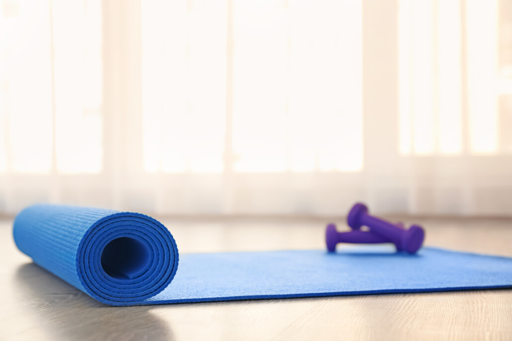 Yoga mat with dumbbells on light floor