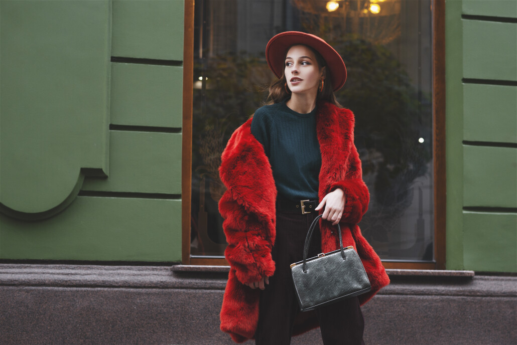 Outdoor fashion portrait of young beautiful confident lady wearing trendy orange faux fur coat, hat, green sweater, holding stylish snakeskin textured handbag, posing in street of city. Copy space