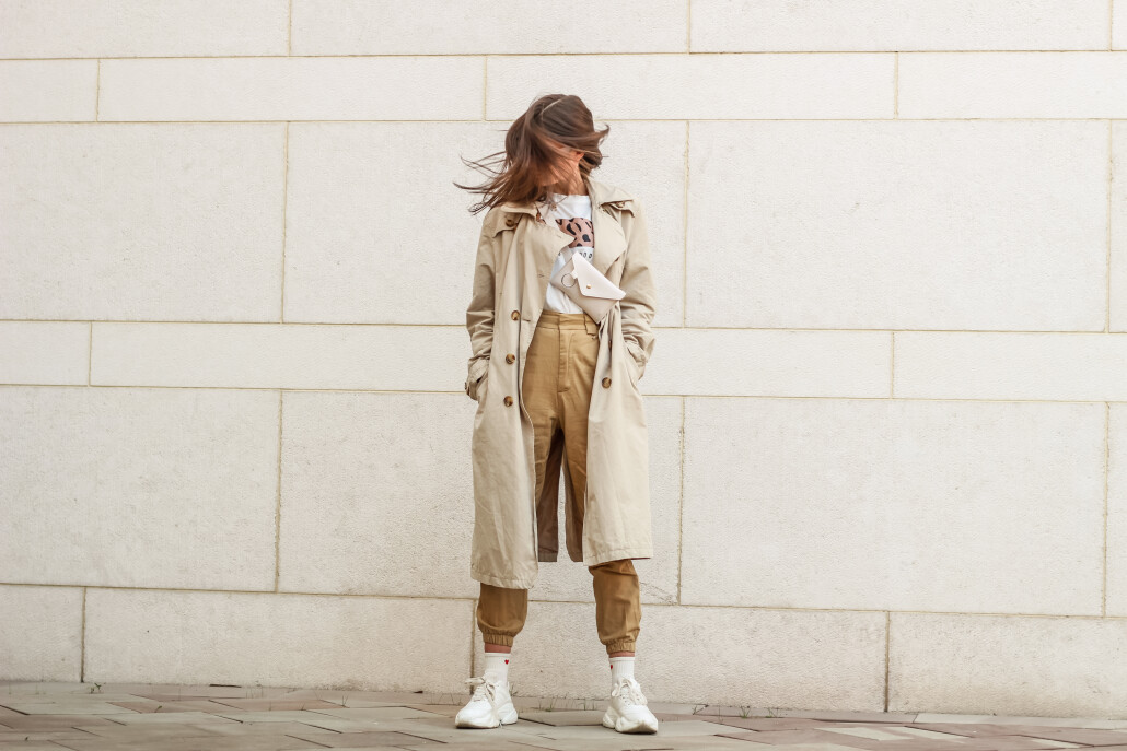 Portrait shooting of a stylish girl. Beige shades. Trends of spring and summer 2019. Pants of cork.Trench cloak, a wide jacket.