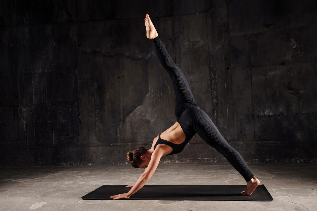 Young caucasian woman exercising yoga or stretching in studio on dark background