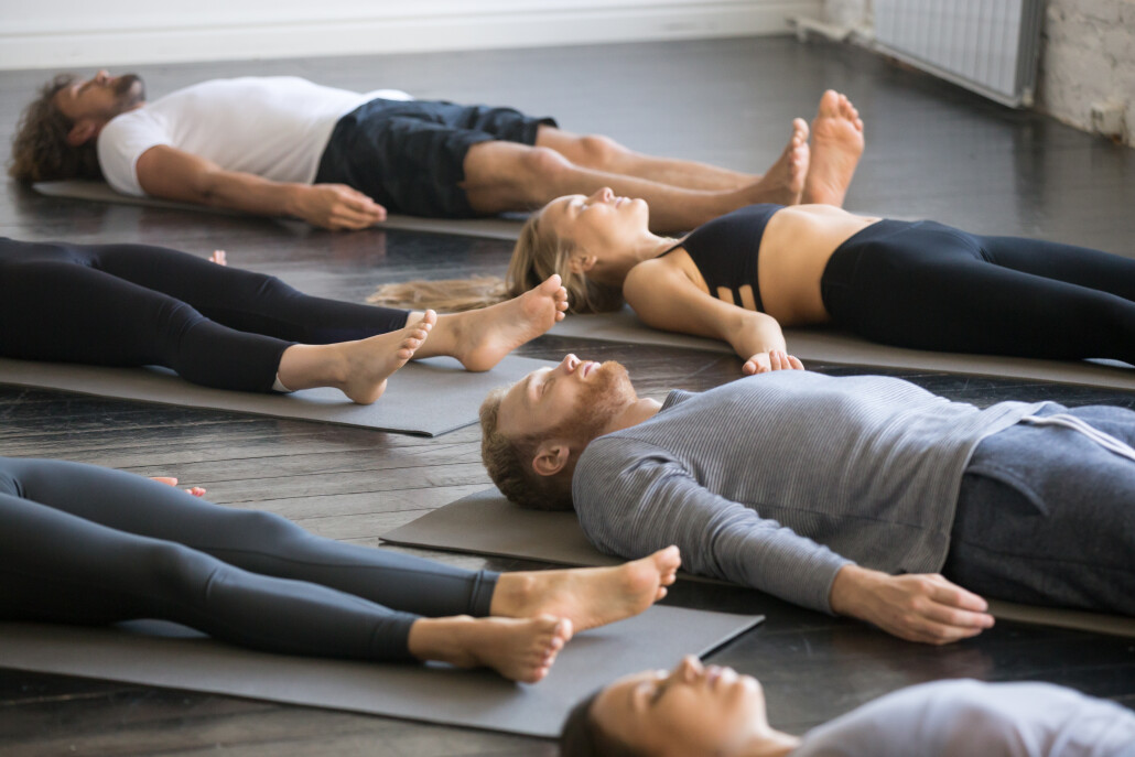 Group of young sporty people in Savasana pose