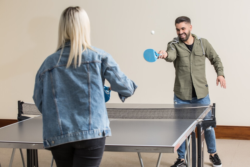 Cheerful friends playing ping pong
