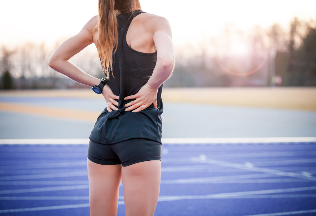 Athlete woman has back pain, muscle injury during running training