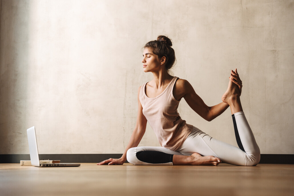 Photo of young concentrated woman doing yoga exercises using laptop while sitting on floor at home