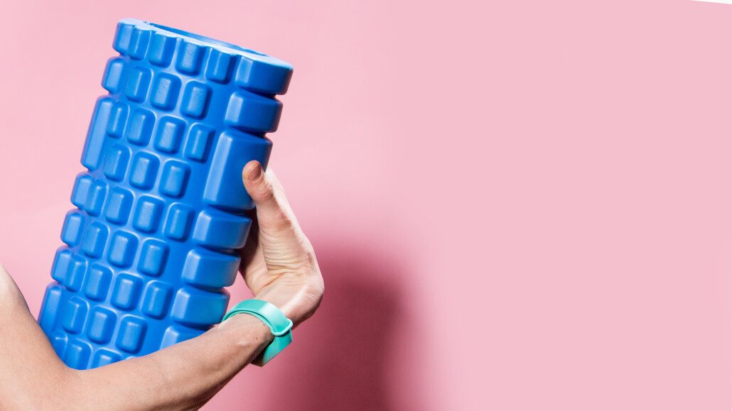 Bright fitness woman. Sport fashion. Funny sport fitness woman with foam roller isolated over pink background