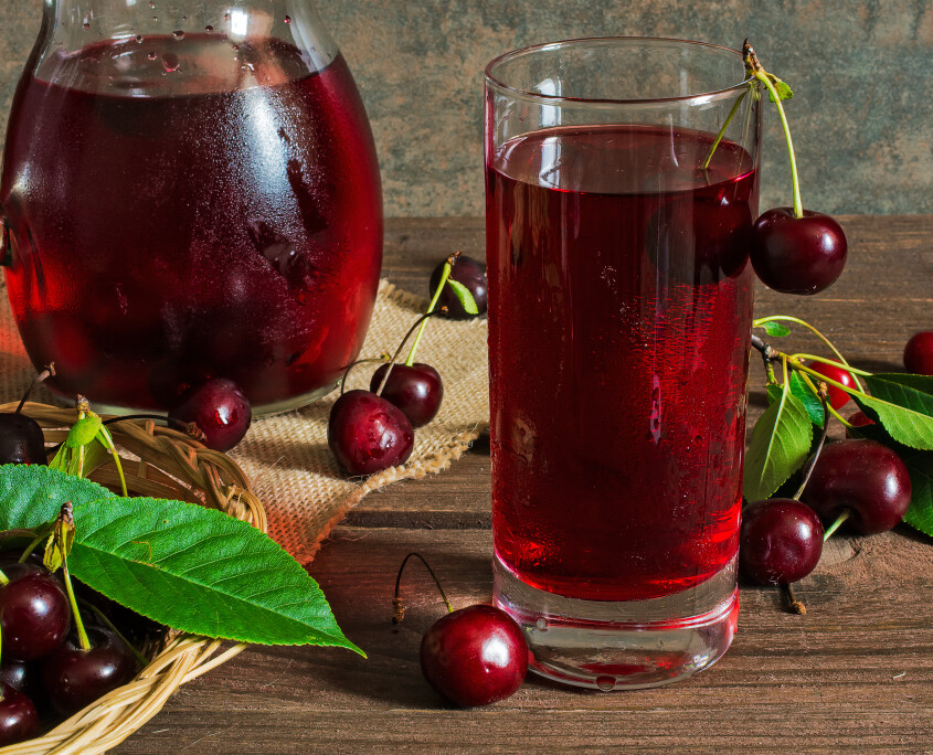 cold cherry juice in a glass and pitcher with cherries inside on wooden tablr