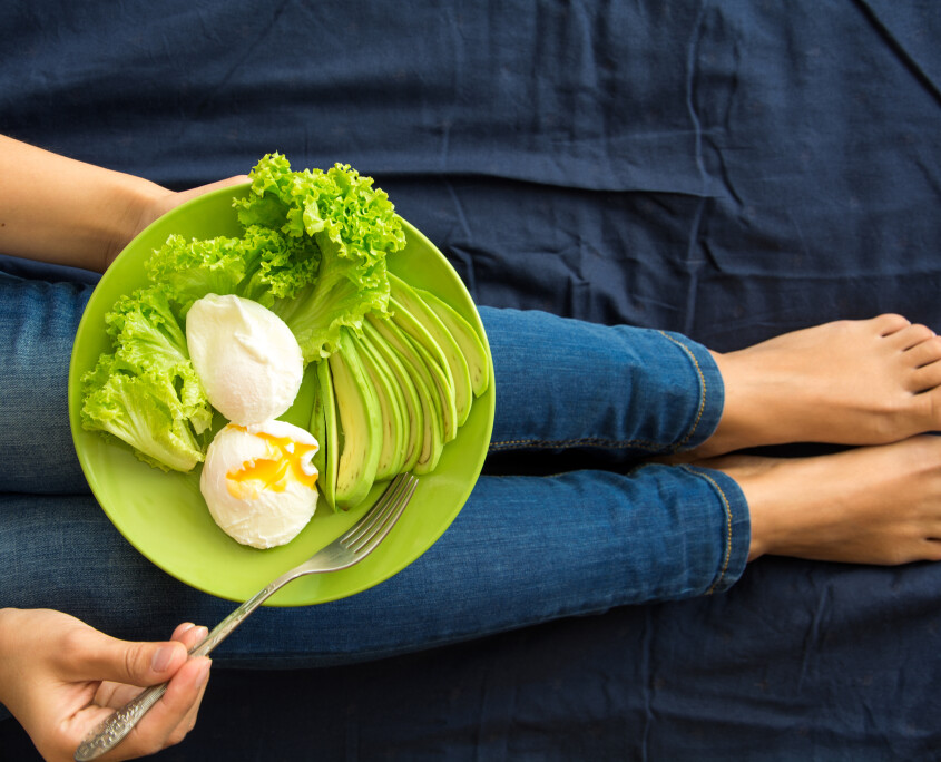 Healthy eating concept. Women's hands holding plate with lettuce, avocado slices and poached eggs. Top view. Toned