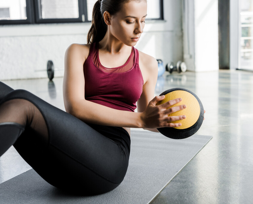 focused fit sportswoman working out on abs with medicine ball at sports center