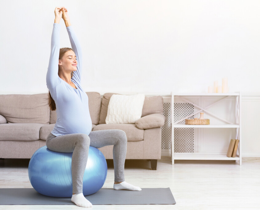 Young pregnant girl sitting on fit ball at home