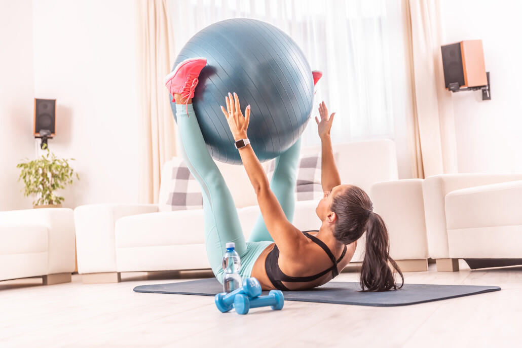 Girl exercising at home rising a swiss ball into the air by her legs, while lying on the floor.