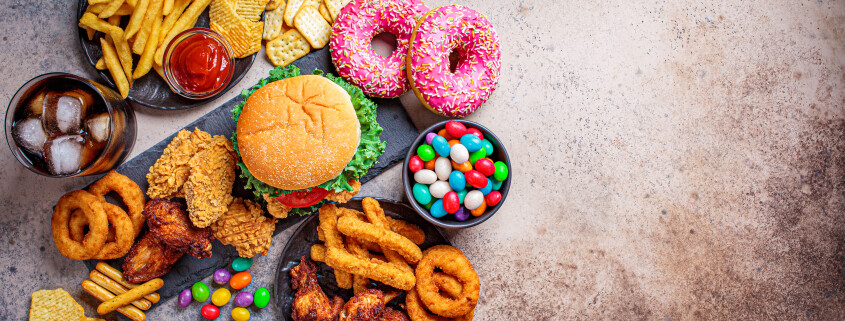 Bunner of fast food assortment. Junk food concept. Unhealthy food for the heart, teeth, skin, figure, top view.