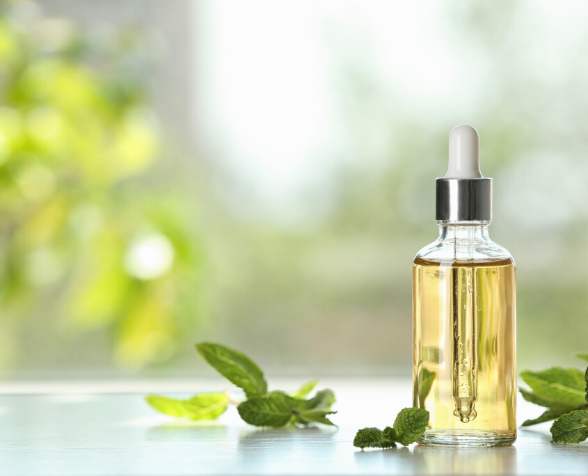 Bottle of mint essential oil on white wooden table against blurred background. Space for text