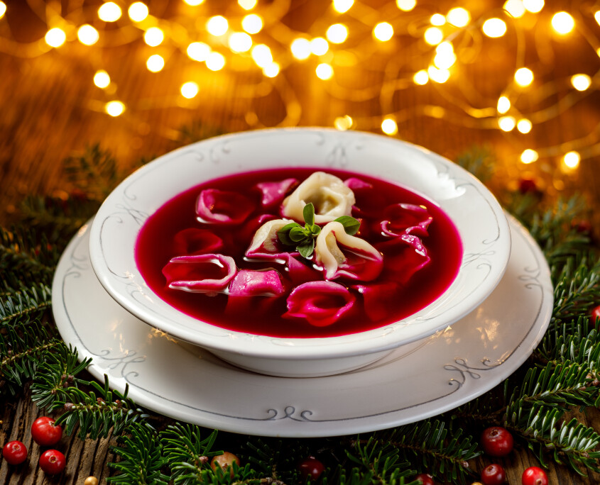 Christmas beetroot soup, red borscht with small dumplings with mushroom filling in a ceramic white plate on a wooden table.Traditional Christmas eve dish in Poland.