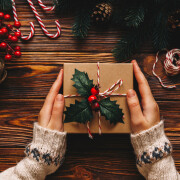 Christmas gift. Congratulations.Top wiew of woman holding traditional decorated gift box. Wooden table with cane,fir branches,fir cone, and berries