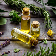 Aromatherapy. Essential oils in small bottles near fresh herbs on dark wooden background