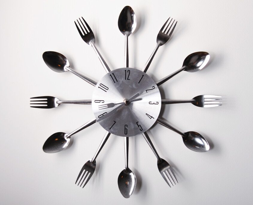 Clock design with spoons and forks over white background