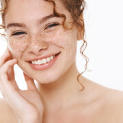 Headshot satisfied tender smiling redhead cute girl freckles curly-haired, standing naked white background laughing happily gently touch cheek look after skin like result apply cosmetology product