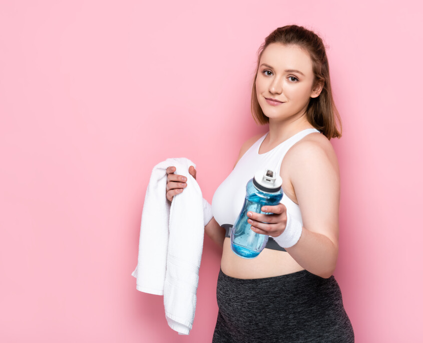 smiling overweight girl holding sports bottle and white towel on pink