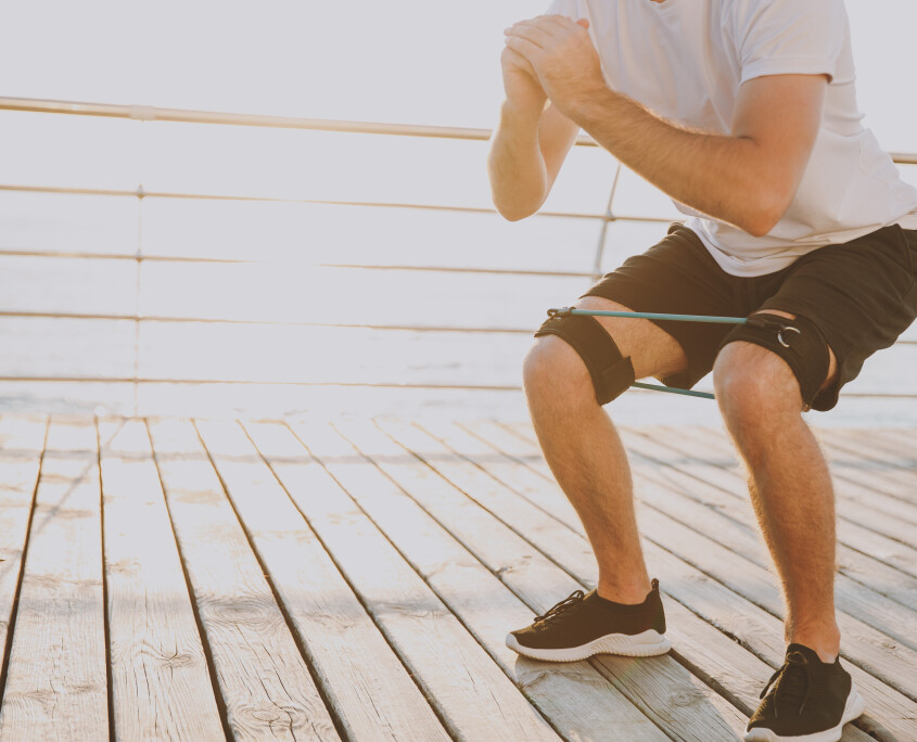 Cropped image of young athletic man guy 20s in white t-shirt black shorts posing training doing exercises for legs with fitness gums at sunrise over the sea outdoors.