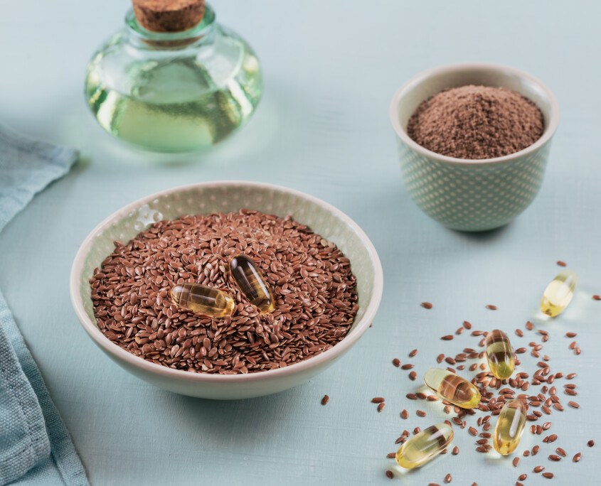 Brown flax seed or linseed and ground or crushed flaxseed in small bowl and gelatin capsules with omega oil on a light blue background.